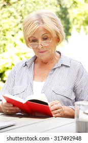 Portrait of a senior woman sitting at home in the garden while reading a book.