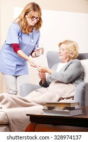 Portrait of senior woman sitting at home and home care nurse giving medication to an elderly woman