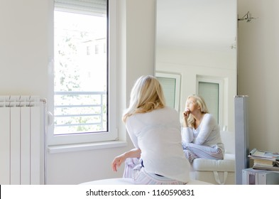 Portrait of senior woman sitting in livingroom, looking through the window and feeling sad and depressed.