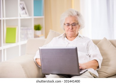 Portrait of senior woman sitting on the couch at home