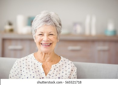 Portrait of senior woman sitting on sofa at home