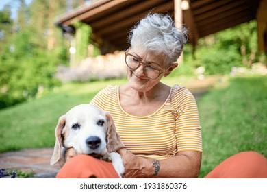Portrait of senior woman sitting outdoors in garden, pet dog friendship.
