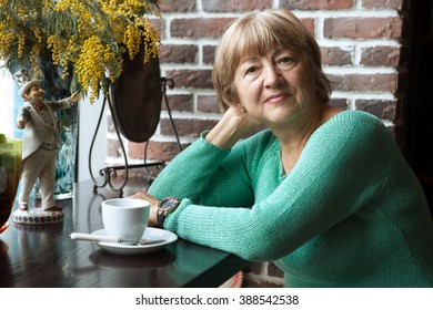 Portrait of senior woman in smart clothes having tea in cafe