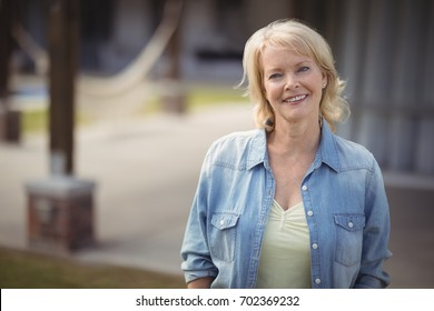 Portrait of senior woman smiling outside her house