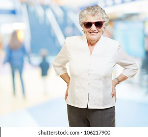 portrait of a senior woman smiling and wearing sunglasses at a mall