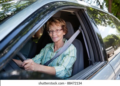Portrait of senior woman smiling while driving car