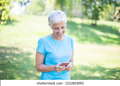 Portrait of senior woman in sports clothing  using smart phone outdoor
