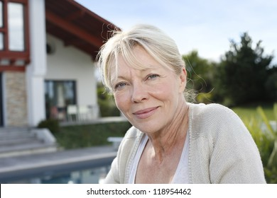 Portrait of senior woman standing in front of home