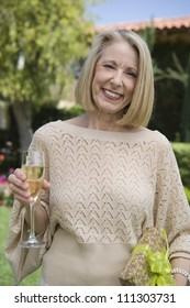 Portrait of senior woman standing with glass of champagne and gift box