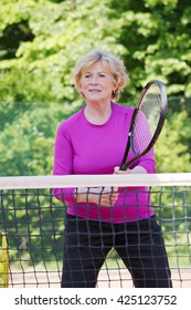 Portrait of senior woman standing at net on tennis court and playing tennis.
