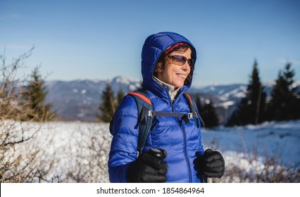 Portrait of senior woman standing in snow-covered winter nature.