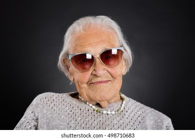 Portrait Of Senior Woman With Sunglasses Over Grey Background