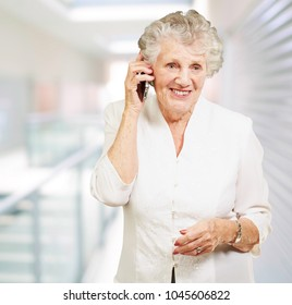 portrait of senior woman talking on mobile at modern office