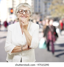 portrait of senior woman thinking and looking up at a crowded place