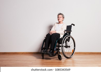 Portrait of a senior woman with wheelchair in a studio. Copy space.