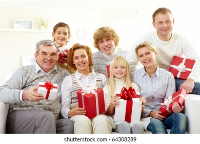 Portrait of senior and young couples and their children with giftboxes