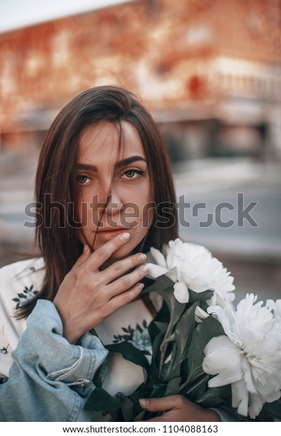 portrait of a sensitive woman with a bouquet of flowers, namely white peonies. girl with short hair, brunette.