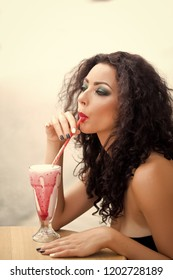 Portrait of sensual attractive cute young woman with curly brown hair and fashion bright makeup looking away sipping cocktail through straw on white background isolated, vertical picture