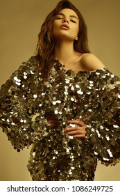 Portrait of a sensual beautiful brunette woman in a shiny fashion dress of sequins posing on a sparkling gold background in studio