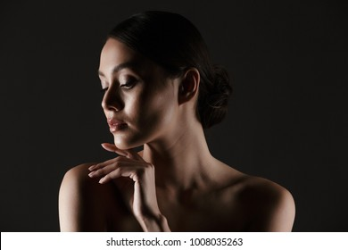Portrait of sensual beautiful woman looking aside while touching her chin in low lights isolated over black background