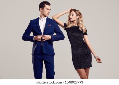 Portrait of sensual beautiful young couple dressed in formal clothes: woman in fashion luxury black dress and man wearing blue classical suit isolated on white background.