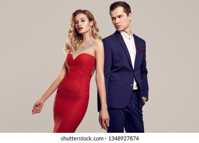 Portrait of sensual beautiful young couple dressed in formal clothes: woman in fashion luxury red dress and man wearing blue classical suit isolated on white background.