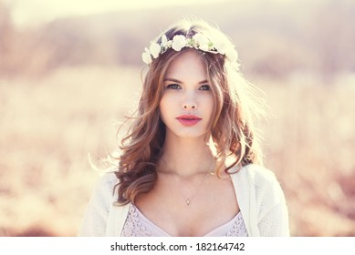 portrait of a sensual blonde with flowers on her head. photo done in the spring on a sunny day field