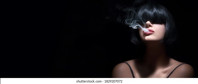 Portrait of a sensual brunette woman with bangs vaping or smoking as smoke curls from between her parted lips with selective focus and shadows over a black panorama background with copyspace