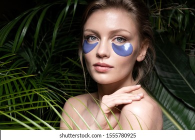 Portrait of sensual girl applying special blue cosmetological patches to keep facial dermis moisturized and clean. Cute lady with charming blue eyes relaxing in spa. Skincare concept