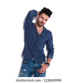 portrait sensual man wearing a navy shirt posing with a hand in pocket and the other his backhead while standing near a white wall