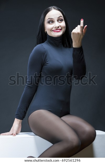 Portrait of Sensual Mid-Aged Caucasian Brunette Woman.Posing With Finger Pointed Forward. Against Black.Vertical Image