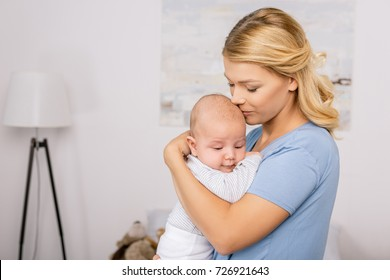 portrait of sensual mother holding baby in hands at home