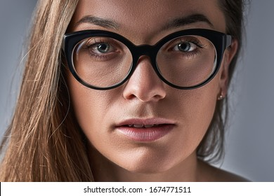 Portrait of sensual serious brunette caucasian woman in black frame glasses