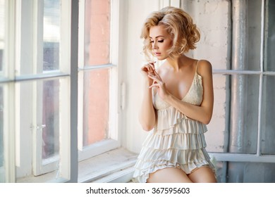 Portrait of the sensual and sexy tender blonde in a white dressing gown, sitting on the window