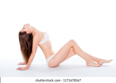 Portrait of sensual tender woman sitting over white background in bra and bikini put hands behind and holding head back demonstrating her perfect body soft skin long hair