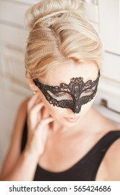 Portrait of sensual woman with luxurious blond hair with mask on face. Sexy style