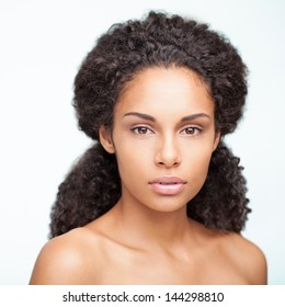 Portrait of a sensual young African woman posing againt a white background.