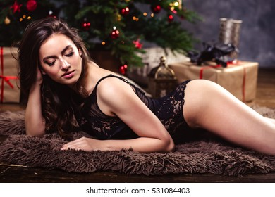 1fbe62977c5 portrait of sensual young woman in a black lingerie over christmas  background