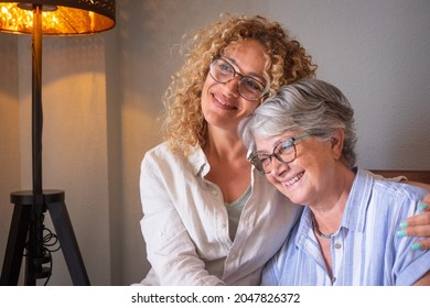 Portrait of serene and smiling senior mother and mature blonde daughter, hugging sitting on sofa at home