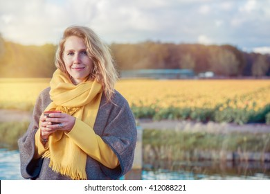 Portrait of a serene woman in  poncho and scarf holding a thermos cup with hot tea in the countryside. In the background  yellow tulip fields are situated.