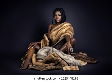A portrait of a serene young black female with long dreadlocks, beautiful makeup and perfect lips sitting by herself on fur in a studio with dark background wearing jewelry & a fur coat.