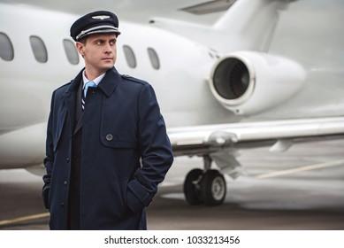 Portrait of serene young pilot putting hands in pocket. He standing opposite plane. Job concept