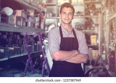 Portrait of serios adult man in uniform who is standing on his workplace in building store