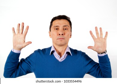 Portrait of a serious adult men dressed in blue sweater with their hands up