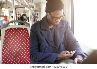 Portrait of serious African American hipster in black stylish hat and coat using smartphone sitting in train near window, typing message to his friend about meeting him at final metro station