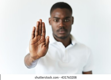 Portrait of serious African American male holding hand in stop sign, warning and preventing you from something bad, looking at the camera with worried expression. Selective focus on the palm