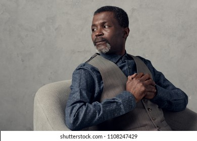 portrait of serious african american man in waistcoat sitting in armchair