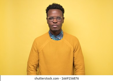 Portrait of serious African American man in yellow sweater with no emotion on face against colored background.