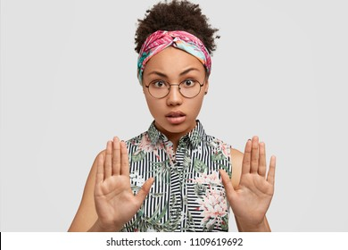 Portrait of serious African American woman shows stop gesture, asks be calm, refuses smoking in company of friends, isolated over white background. People, body language and ethnicity concept