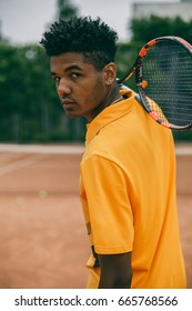 Portrait of serious african man holds a tennis racket on his shoulder. Back view portrait of a man playing in tennis outdoors.